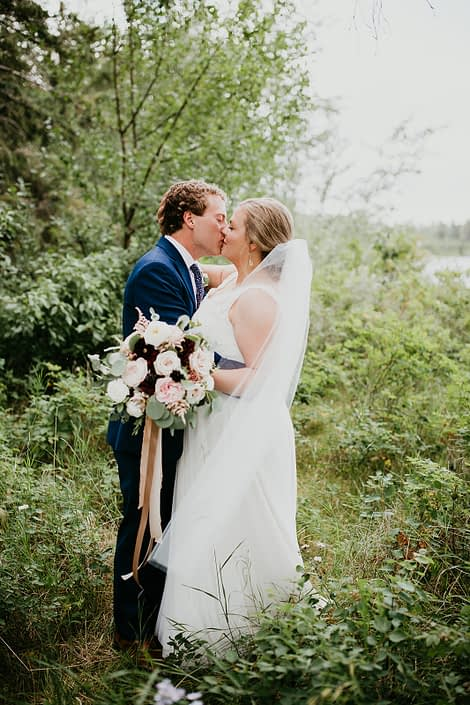 Bride kissing groom and holding a jewel tone bridal bouquet designed with burgundy dahlias, keira garden roses, white ranunculus, amnesia roses, quicksand roses, blackberry scoop scabiosa, light pink astilbe and eucalyptus greenery.