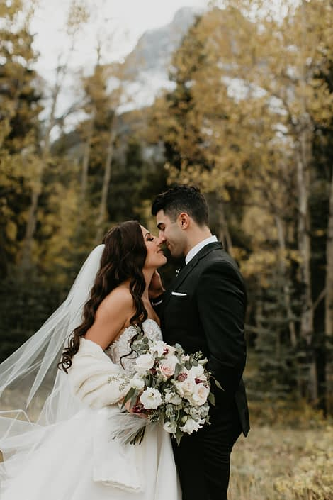Elegant Canmore Wedding - Brittany and Briggs almost kissing with blush and ivory bridal bouquet made of burgundy astrantia, quicksand roses, white o'hara garden roses, lisianthus, ranunculus and eucalyptus