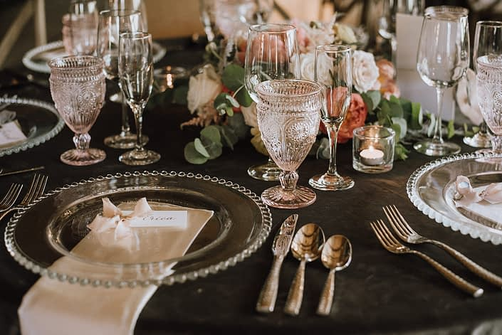 Place setting with clear and blush tableware, silverware, stationary, linens and a low coral and blush flower arrangement featuring roses and coral charm peonies.