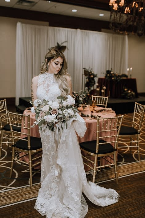 Cambridge Bridal Show 2020 - model wearing lace gown and carrying a bridal bouquet of blush and ivory roses with greenery and trailing ribbons.