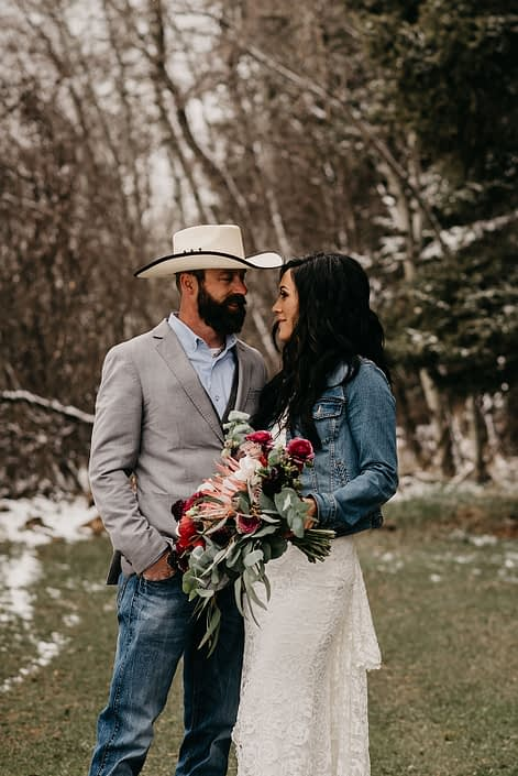 Rustic Boho Chic Wedding - Bride and groom standing together. Groom wearing cowboy hat, sport coat and jeans. Bride wearing ivory lace dress and jean jacket holding bridal bouquet made of king protea, red peonies, pink roses, plum scabiosa, panda anenome, and eucalyptus greenery.