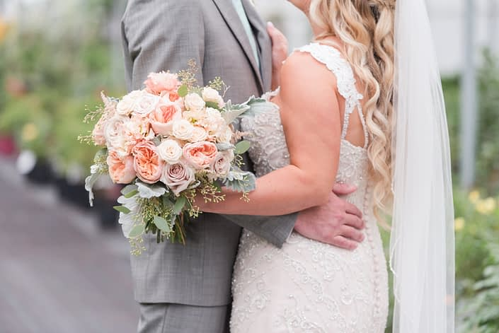 Bride and groom Megan and Steven embracing while Megan carries a blush pink bridal bouquet featuring apricot lisianthus, Juliet garden roses, dusty miller and eucalyptus.