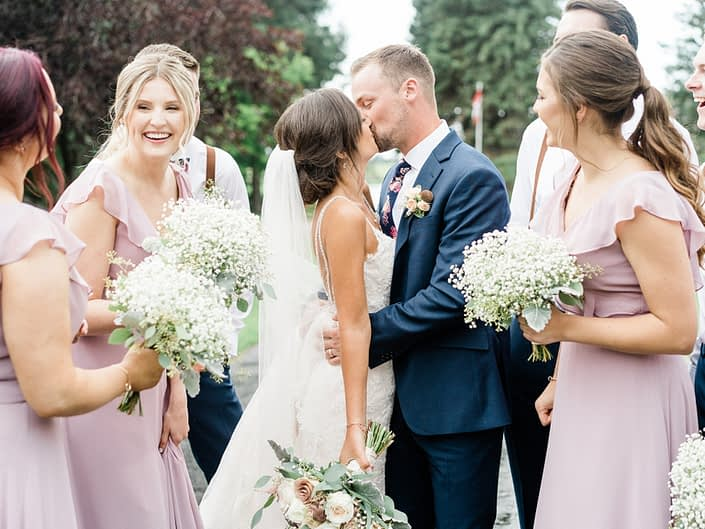 Bride and groom kissing surrounded by bridal party; bride is holding rose gold and dusty rose bridal bouquet; bridesmaids are wearing elegant rustic dusty rose dresses and carrying babies breath bouquets.