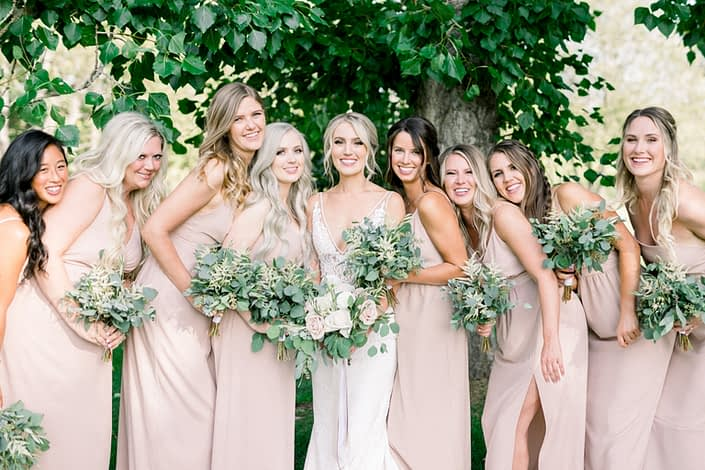 Kayla wearing a white bridal gown and holding a bridal bouquet featuring white o'hara garden roses, white ranunculus, quicksand roses, white astilbe, olive branches and eucalyptus surrounded by her bridesmaids wearing blush floor-length dresses and holding simple bouquets made of white astilbe, olive branches and eucalyptus greenery.