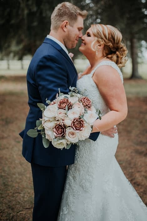 Bride and Groom holding bridal bouquet of rose gold succulents and garden roses and eucalyptus in a summer wedding