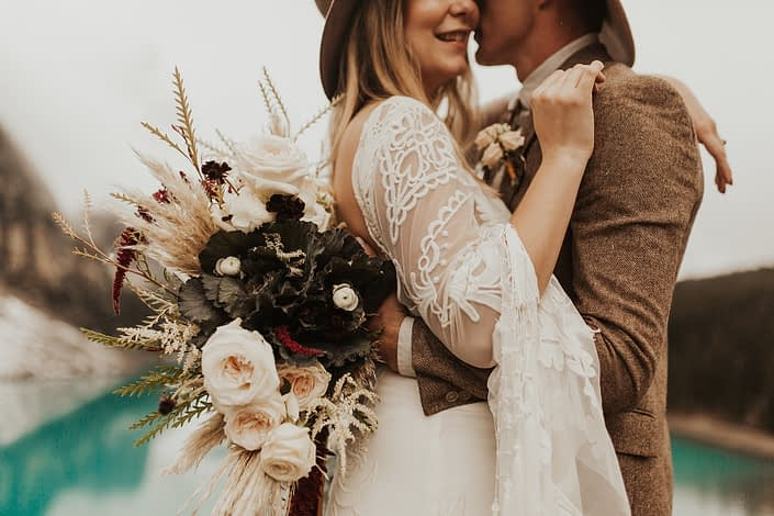 Moraine Lake Elopement Styled Shoot - male model wearing a hat and an ivory boutonniere, brown jacket and bolo tie. Girl wearing a hat and an ivory lace bridal gown while holding pampas grass bouquet with blush roses and pops of red flowers