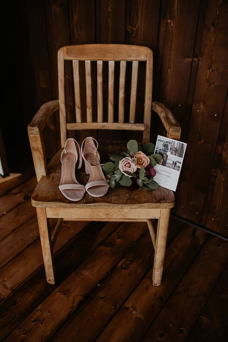 Bride's shoes, wedding invite and a small bouquet atop a chair.