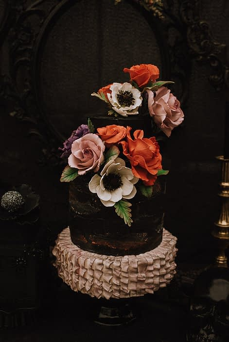 alternative wedding cake with sugar anemone red roses and mauve roses on black cake