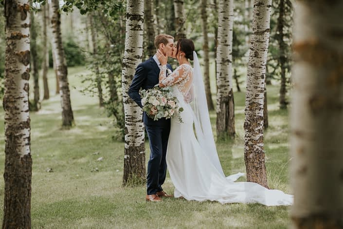 Bride and groom kissing amongst trees with bride's bouquet