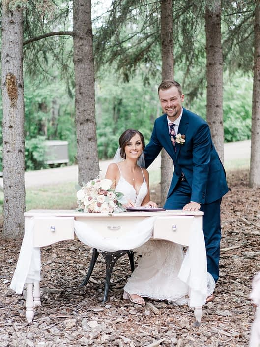 Bride and groom at the signing table; groom is wearing a rose gold boutonniere and bride has her dusty rose bridal bouquet featuring blush, cream and rose gold florals with grey toned greenery.