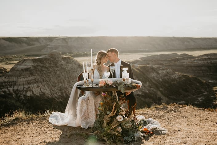 bride and groom at sweetheart table overlooking the drumheller badlands with driftwood floral accents