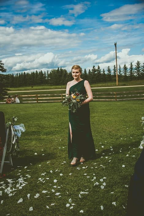 Bridesmaid wearing green dress and holding bouquet designed with plum dahlias, juliet garden roses, white ranunculus, golden mustard roses, olive branches and eucalyptus.