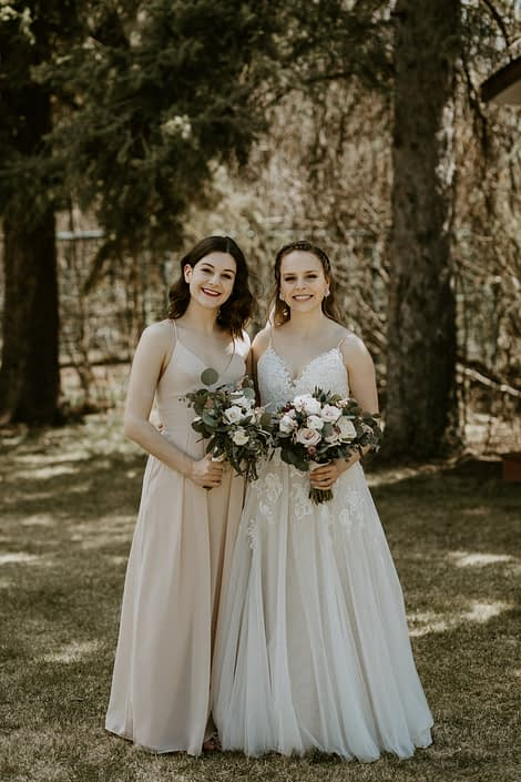 Bride and bridesmaid with blush, white and burgundy bouquets