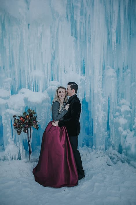 Ice castles engagement photos with burgundy taffeta skirt and bridal bouquet in burgundy
