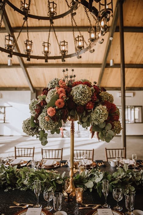 tall centerpiece on top of a gold candelabra with green hydrangea and red dahlia and red roses and orange dahlia accented by a mixed greenery garland on the long table at canyon ski resort in Red Deer Alberta