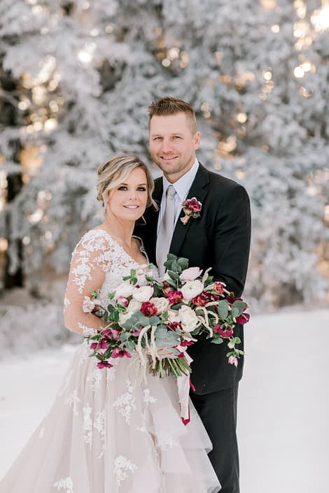 Bride and groom with blush and burgundy flowers for winter photoshoot