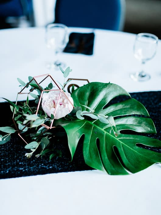 Centrepiece made of monstera leaf, blush peony, and a mixed variety of eucalyptus in a metallic geometric display.