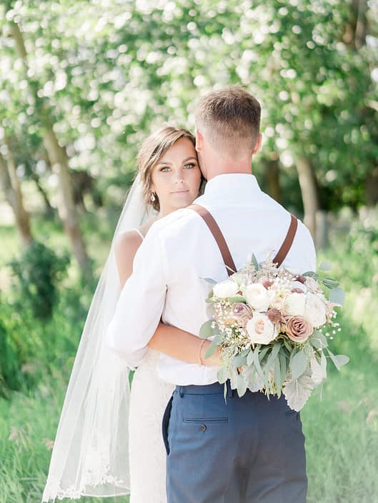 Bride hugging groom and holding bouquet designed with rose gold painted scabiosa pods, white o'hara garden roses, dusty pink amnesia and quicksand roses, astilbe, raununculus, babies breath, dusty miller and eucalyptus.