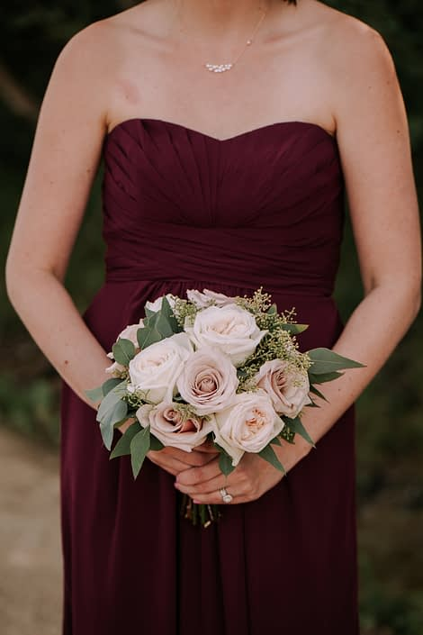 Bridesmaid wearing burgundy dress and holding blush bouquet designed with white ohara garden roses, quicksand roses and eucalyptus.
