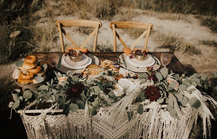 Sweetheart table with charcuterie, donuts, flowers and wooden chairs; boho