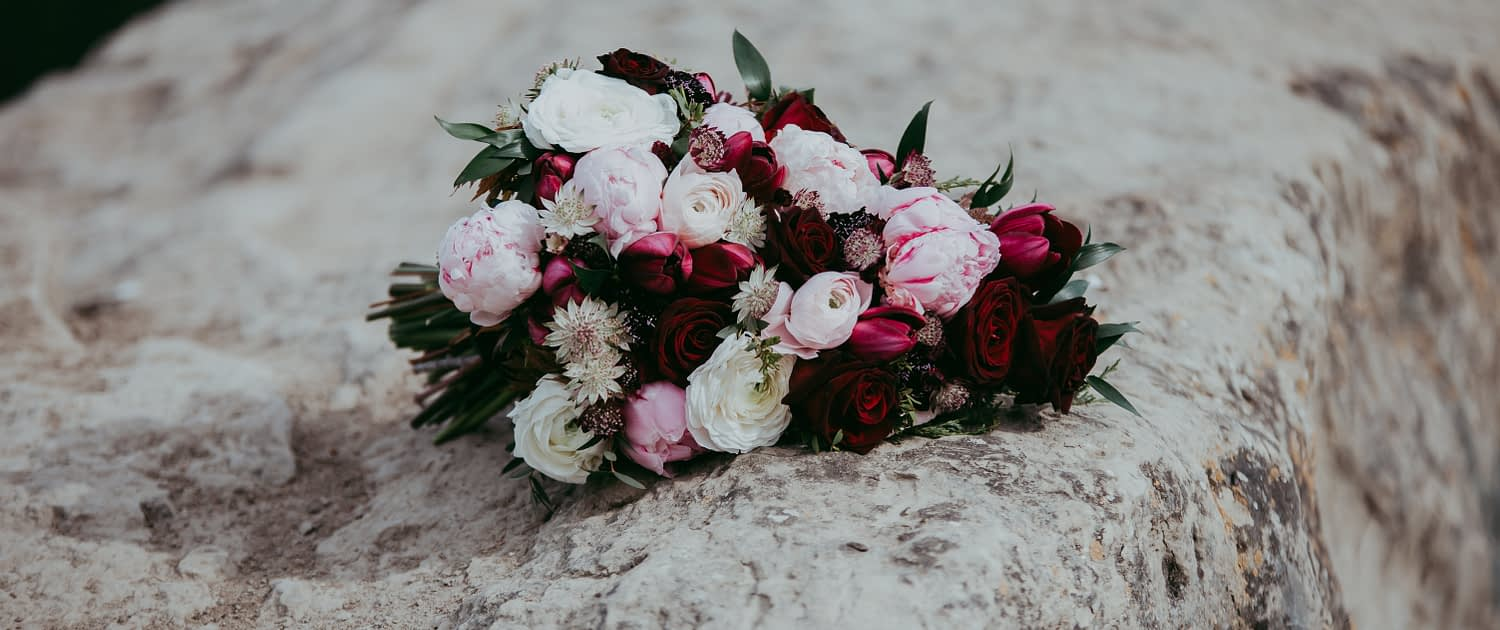 Pink and burgundy bouquet featuring burgundy helleborus, Sarah Bernhardt peonies, blush and white ranunculus, black baccara roses, blackberry scoop scabiosa, burgundy tulips and pale pink astrantia with maple leaves, juniper, purple sage eucalyptus greenery.
