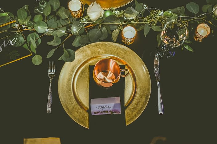 Black and gold table setting with a moscow mule mug as a wedding favour. A fresh eucalyptus greenery garland with twinkly lights ran down the centre of the table.
