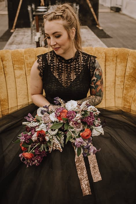 alternative bride in black wedding dress with tattoos on a yellow sofa with a bouquet of red ranunculus and amnesia roses and white anemone and white pieris and plum scabiosa and clematis