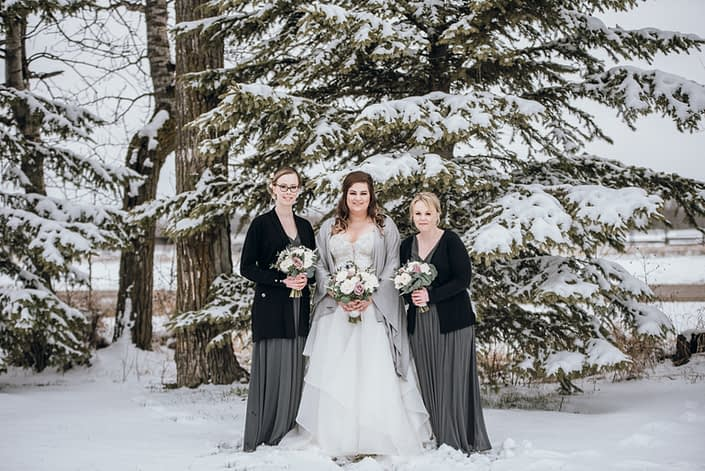 Mauve and Navy winter wedding; bride and bridesmaids wearing black, grey and white and carrying mauve and ivory bouquets accented by navy