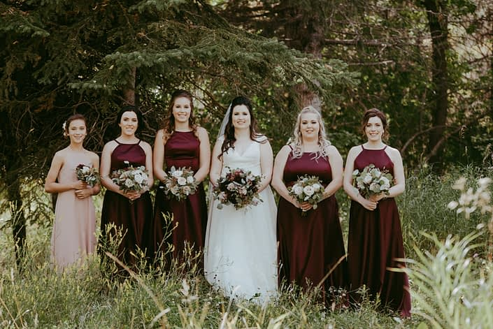 Burgundy and dusty rose bride and bridesmaids; bridesmaids wearing burgundy dresses with blush bouquets; bride with burgundy and dusty rose bridal bouquet; flower girl wearing dusty rose with burgundy and dusty rose bouquet