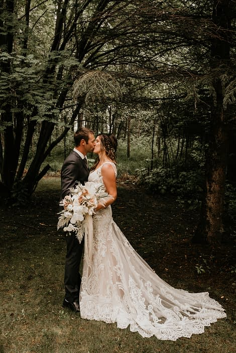 blush and white Rustic Boho Bride and Groom kissing in the woods with blush and white bridal bouquet