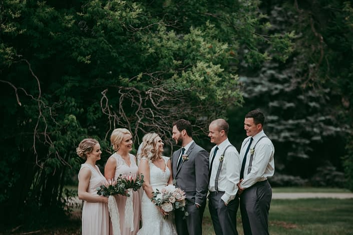 wedding party in blush and charcoal grey with bouquets of pale pink king protea and eucalyptus groomsmen in white shirts and suspenders with boutonnieres