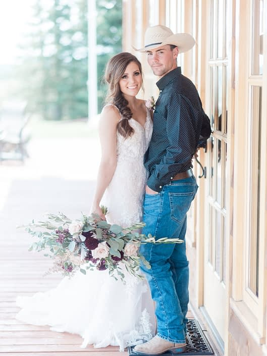 Bride and cowboy groom with oblong country chic bridal bouquet.