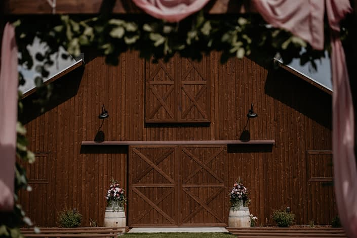 Sweet haven barn with barrels topped with floral arrangements.