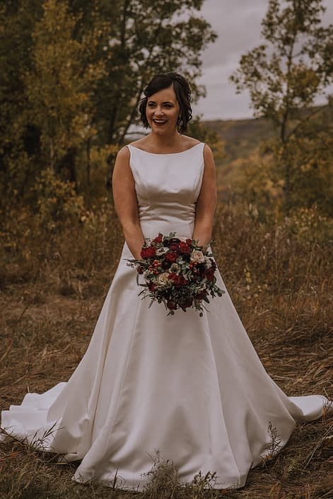 bride in Kleinfelds ivory wedding dress holding a bridal bouquet of burgundy and navy flowers with eucalyptus greenery