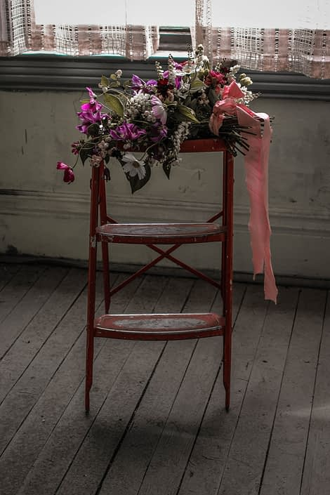 Pink Vintage Photoshoot - White, pink and purple wildflower bouquet made of cosmos and greenery tied with trailing ribbons atop a red ladder.