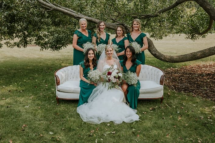 bride and bridesmaids in forest green sitting on an antique ivory and wood sofa holding bridesmaid bouquets of babies breath and brides bouquet of burgundy dahlia, blush roses and ivory roses and eucalyptus