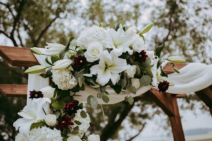 Close up of rustic archway arrangement with white voile and designed with hydrangea, roses, lilies and burgundy dahlia