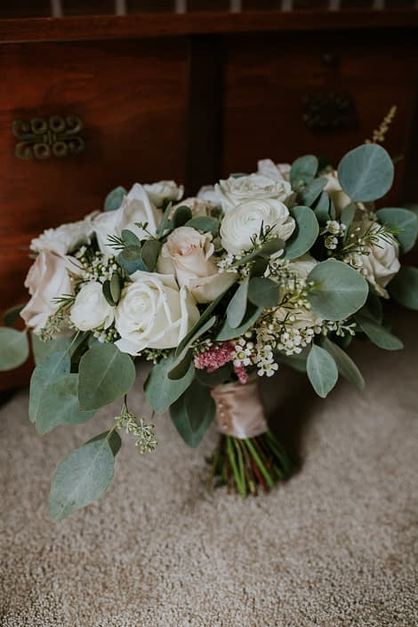 Brooke's ivory and blush pink bridal bouquet made with White O'hara garden roses, quicksand roses, white ranunculus, astilbe, white playa blanca roses, waxflower and mixed eucalyptus greenery.