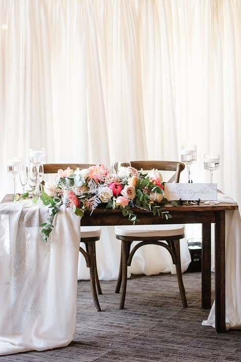 """Wooden sweetheart table for Canyon Ski Resort Open House 2019 with floating candles, a marble """"better together"""" sign, and a large arrangement designed with coral charm peonies, quicksand roses, playa blanca roses, peach ranunculus, light pink astilbe, silver plumosa, salal and a variety of eucalyptus greenery."""