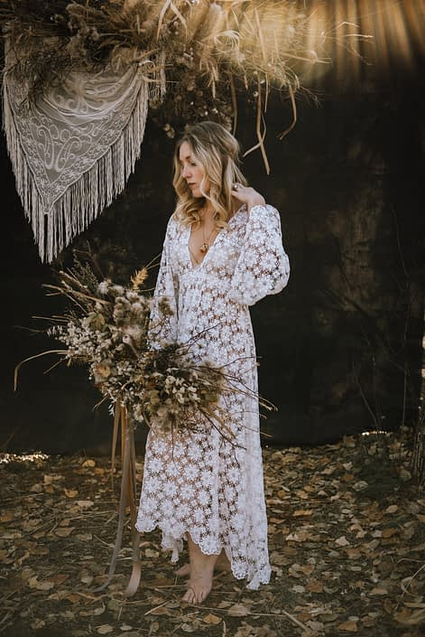 sunburst boho bride in the fall in the woods barefoot with a foraged bouquet made of dried dandelions and twigs ad fall toned trailing ribbons