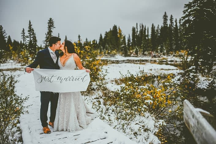 Meagan and Dwayne kissing in the snowy Rocky Mountains while holding a Just Married sign.