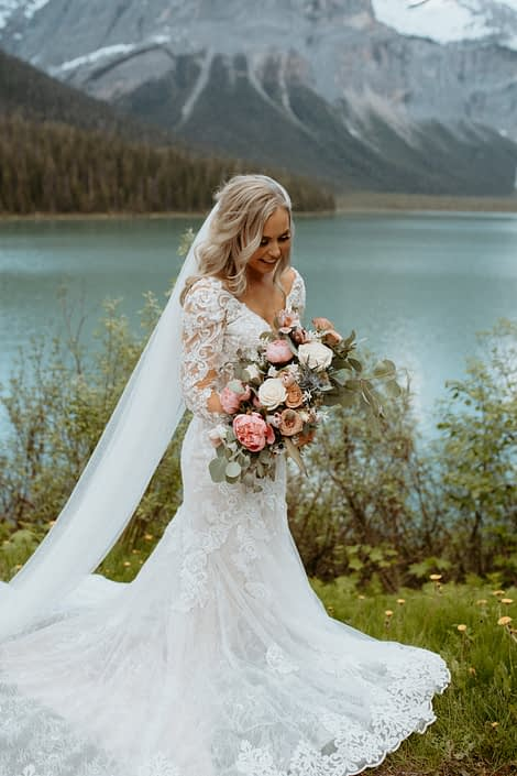 Bride with pink and white bridal bouquet featuring peonies, roses, tulips and eryngium in the Rocky Mountains