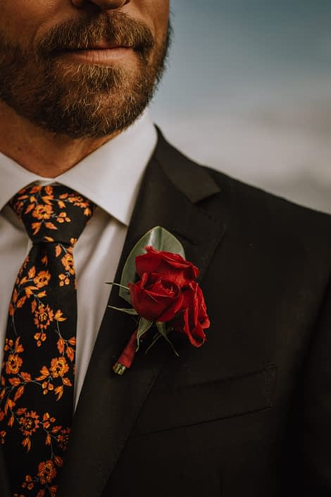 bearded groom wearing floral tie with red spray rose boutonniere