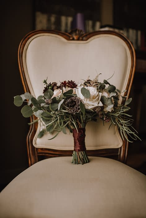 ntique ivory chair with burgundy plum and ivory bridal bouquet with eucalyptus