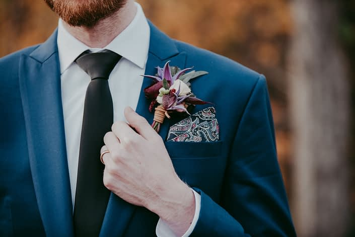 Groom in navt blue suit with paisley pocket square with leather wrapped boutonierre designed with purple clematis and blush spray rose