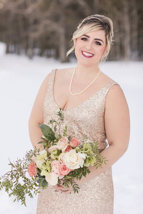 Winter Bridesmaid in blush sequin dress with oblong bridesmaid bouquet in ivory and peach roses