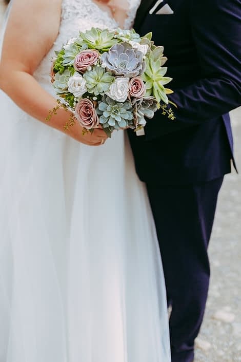Bride bouquet f succulents and mauve amnesia roses held by bride and groom