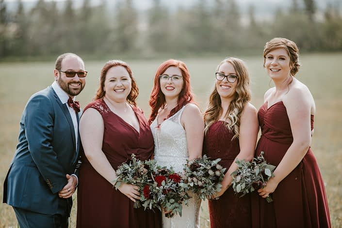 Hailey's burgundy and royal blue bridesmaids and bridesman with bouquets designed with burgundy astrantia, chocolate cosmos, eryngium, burgundy ranunculus, black bacarra roses, blue viburnum berries and eucalyptus