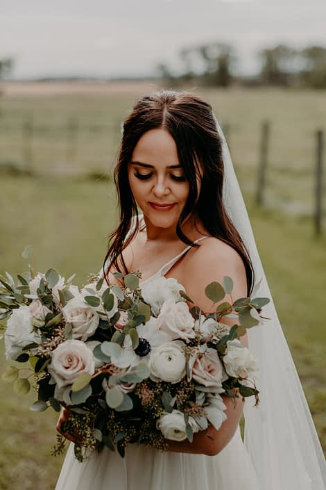 Bride Erika looking at her blush, ivory and white bridal bouquet featuring quicksand roses, ranunculus, panda anemones, lisianthus and mixed eucalyptus.