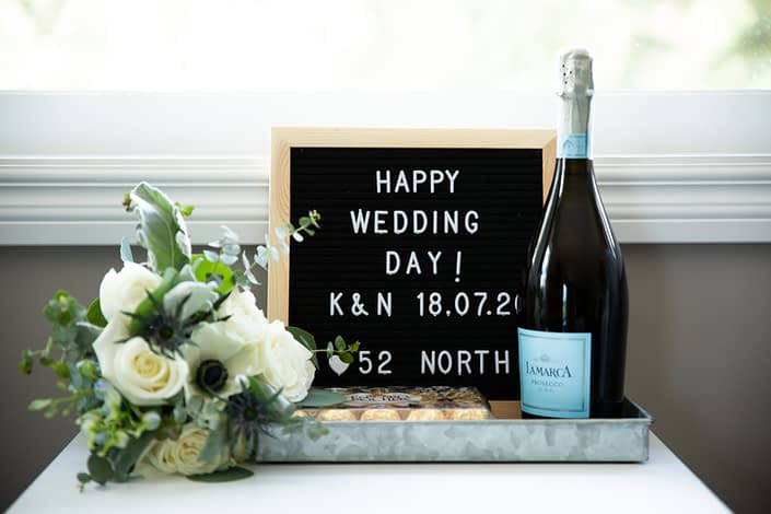 Throw bouquet beside wedding sign and champagne